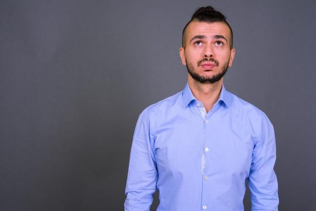 Foto de estudio de guapo empresario turco contra un fondo gris