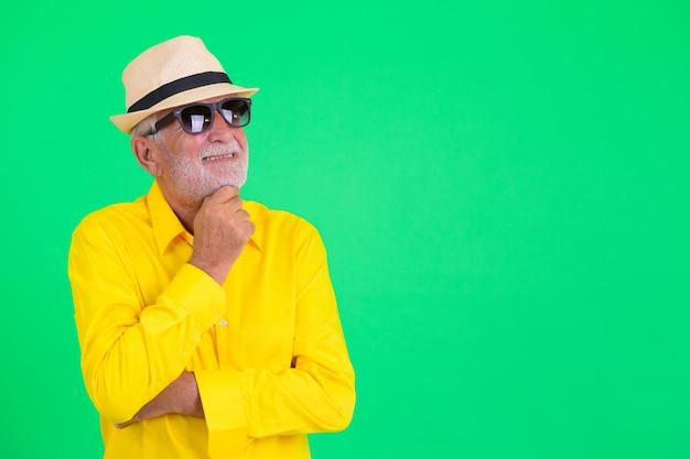 Foto de estudio de guapo turista senior barbudo contra el fondo verde