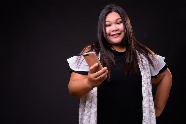 Foto de estudio de hermosa mujer asiática con sobrepeso contra fondo negro