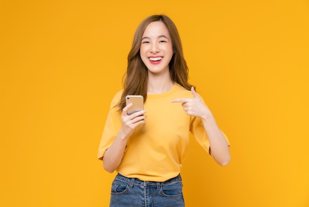 Foto de estudio de hermosa mujer asiática sosteniendo smartphone y sonriendo sobre fondo amarillo claro