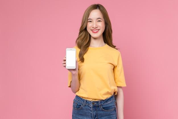 Foto de estudio de hermosa mujer asiática sosteniendo smartphone y sonriendo sobre fondo rosa claro