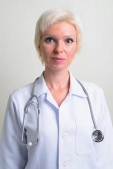 Foto de estudio de hermosa mujer rubia médico con pelo corto contra el fondo blanco.