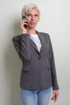 Foto de estudio de hermosa rubia empresaria con pelo corto contra el fondo blanco.