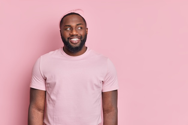Foto de estudio de hombre afroamericano de piel oscura con barba espesa mira con alegría a un lado de estar de buen humor
