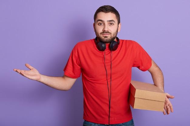 Foto de estudio del hombre barbudo caucásico vestido con camiseta casual roja de pie aislado sobre lila con caja de cartón en la mano, no sabe la dirección exacta de entrega y separando su mano.