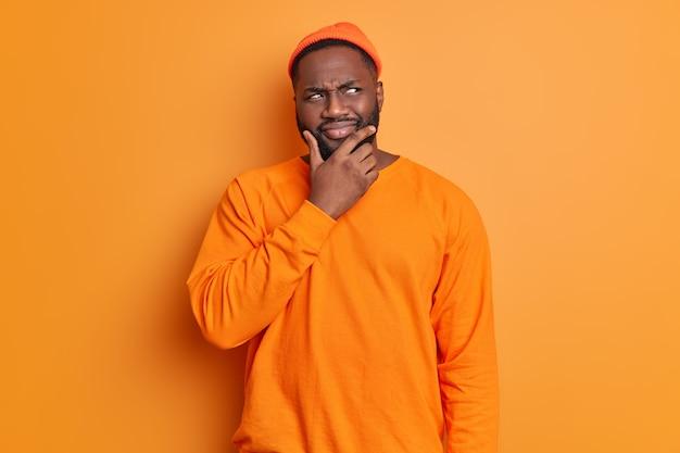 Foto de estudio de hombre guapo con barba sostiene la barbilla mira pensativamente a un lado piensa profundamente sobre algo lleva sombrero y poses de suéter contra la pared de color naranja vivo brillante