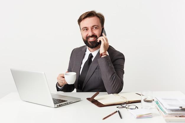 Foto de estudio de un hombre moreno barbudo bastante positivo con corte de pelo corto sentado en la mesa de trabajo con una taza de café, haciendo una llamada con su teléfono inteligente y mirando a un lado con una amplia sonrisa