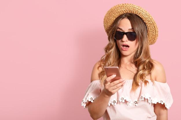 Foto de estudio interior de joven mujer rubia sorprendida con la boca abierta, sosteniendo el dispositivo en una mano, usando su teléfono inteligente rosa, con accesorios de verano. copiar espacio para publicidad.