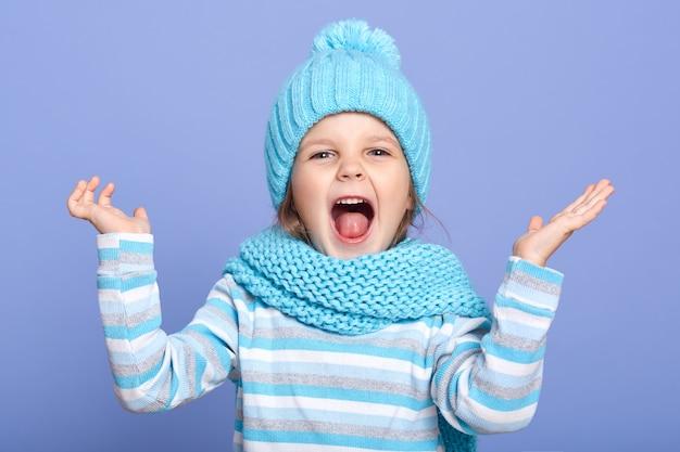 Foto de estudio interior de juguetona divertida niña de pie aislado sobre fondo azul, levantando las manos, abriendo la boca ampliamente, divirtiéndose solo. concepto de niños y juegos.