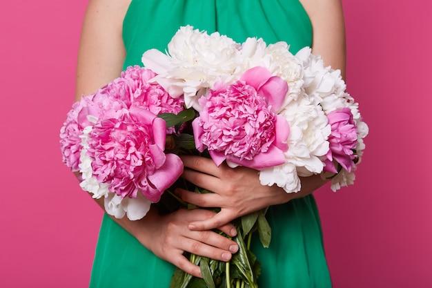 Foto de estudio interior de ramo de peonías blancas y rosas, mujer con vestido verde