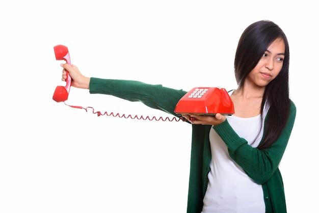 Foto de estudio de joven adolescente asiática sosteniendo teléfono antiguo