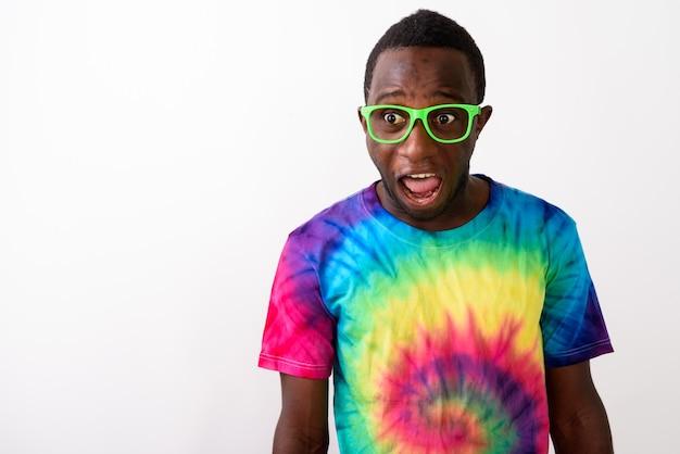 Foto de estudio de joven africano negro sorprendido mirando consternado
