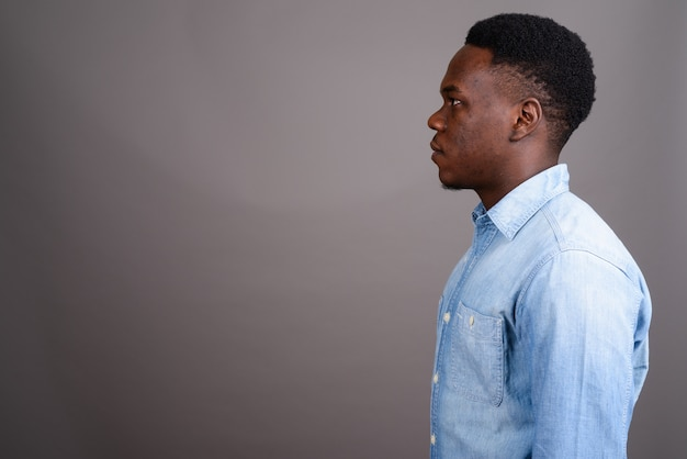 Foto de estudio de joven africano vistiendo camisa de mezclilla contra un fondo gris