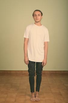 Foto de estudio de joven apuesto hombre vestido con camisa blanca en color