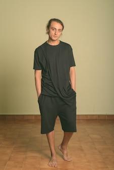 Foto de estudio de joven apuesto hombre vestido con camisa negra en color