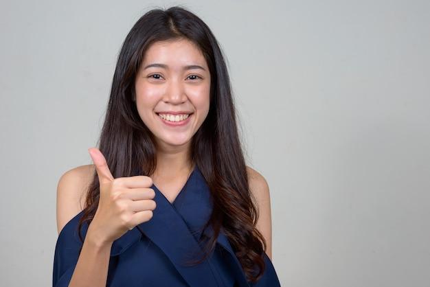 Foto de estudio de la joven y bella empresaria asiática contra el fondo blanco.
