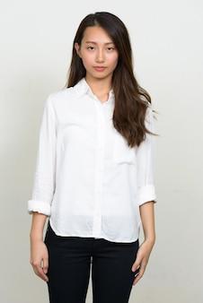 Foto de estudio de la joven y bella empresaria coreana contra el fondo blanco.