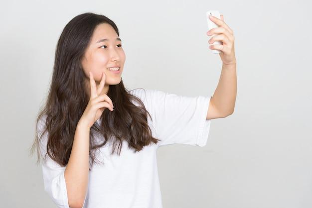 Foto de estudio de la joven y bella mujer coreana contra el fondo blanco.