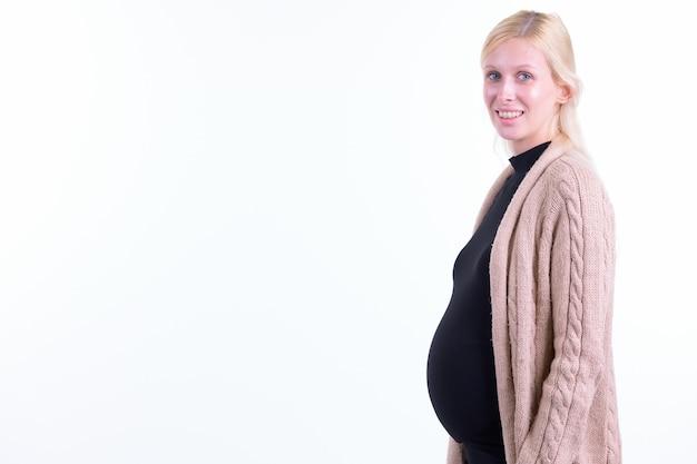 Foto de estudio de la joven y bella mujer embarazada con cabello rubio aislado sobre fondo blanco.
