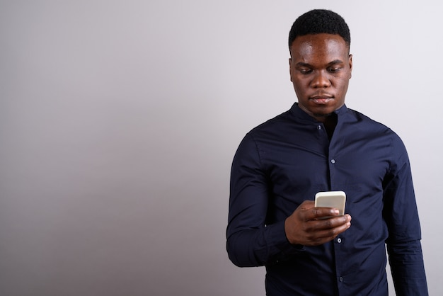 Foto de estudio del joven empresario africano con teléfono móvil contra el fondo blanco.