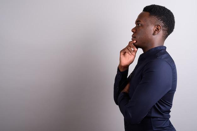 Foto de estudio del joven empresario africano vistiendo camisa azul contra el fondo blanco.