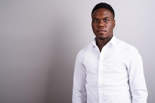 Foto de estudio del joven empresario africano vistiendo camisa blanca contra el fondo blanco.