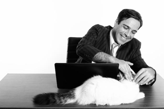 Foto de estudio del joven empresario persa sentado detrás de un escritorio de madera aislado, blanco y negro