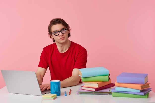 Foto de estudio de un joven con gafas viste una camiseta roja, el estudiante se sienta junto a la mesa y trabaja con libros y un cuaderno, preparado para el examen, con mirada seria, aislado sobre fondo rosa.