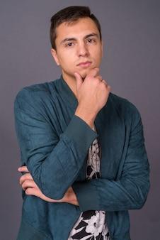 Foto de estudio de joven guapo contra un fondo gris