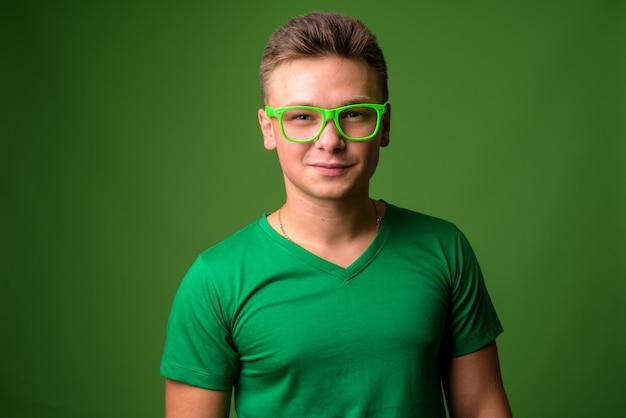 Foto de estudio de joven guapo contra fondo verde