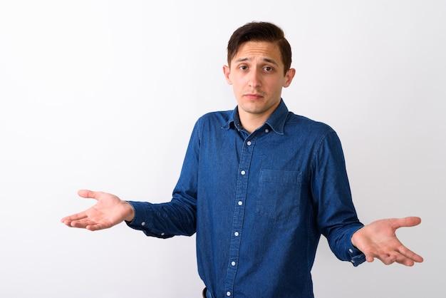 Foto de estudio de joven guapo mirando confundido con ambos brazos
