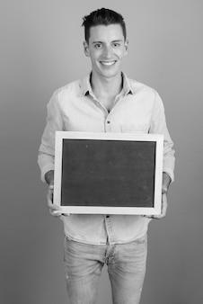 Foto de estudio de joven guapo sosteniendo pizarra contra un fondo gris en blanco y negro
