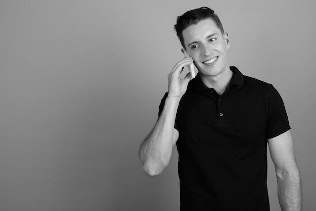 Foto de estudio de joven guapo con teléfono móvil contra un fondo gris en blanco y negro
