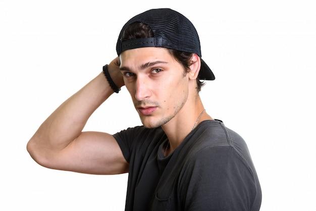 Foto de estudio de joven guapo vistiendo snapback mientras posa