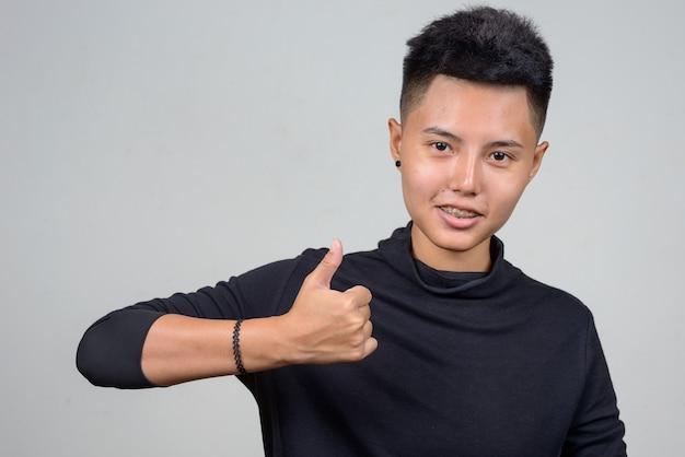 Foto de estudio de la joven mujer lesbiana asiática con pelo corto contra el fondo blanco.