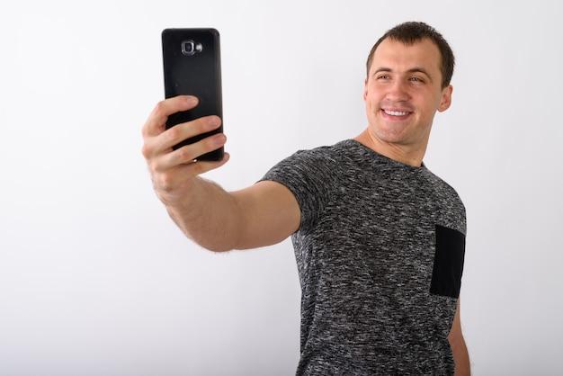 Foto de estudio de joven musculoso feliz sonriendo mientras toma sel