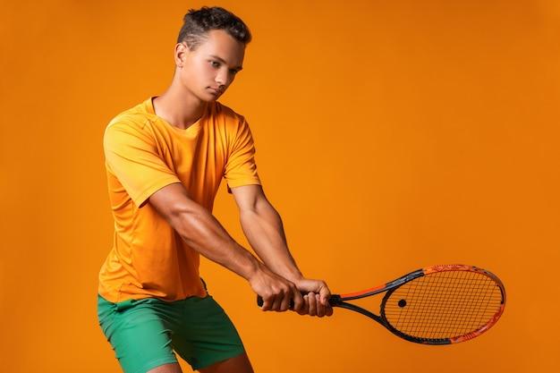 Foto de estudio de un joven tenista sosteniendo la raqueta contra el fondo naranja