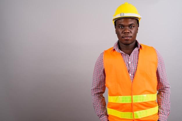 Foto de estudio de joven trabajador de la construcción africana contra el fondo blanco.
