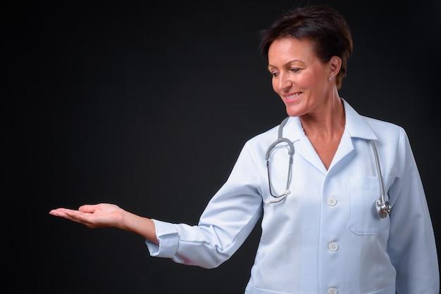 Foto de estudio de madura hermosa doctora escandinava con pelo corto sobre fondo negro