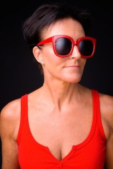 Foto de estudio de madura hermosa mujer escandinava con pelo corto sobre fondo negro
