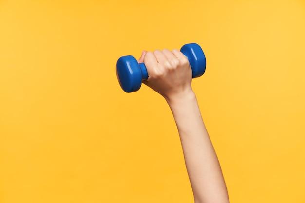 Foto de estudio de mancuerna azul mantenida por mano de mujer de piel clara mientras hace ejercicio para brazos, aislado sobre fondo amarillo. concepto de deporte y cuidado corporal