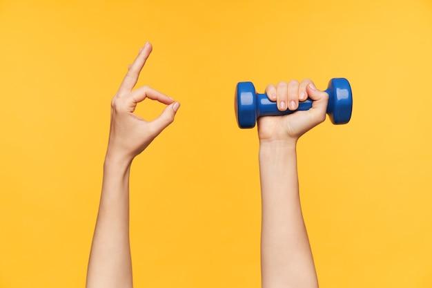 Foto de estudio de la mano de la mujer joven formando con los dedos gesto ok mientras sostiene la mancuerna azul en otro, aislado contra el fondo amarillo. concepto de fitness y entrenamiento
