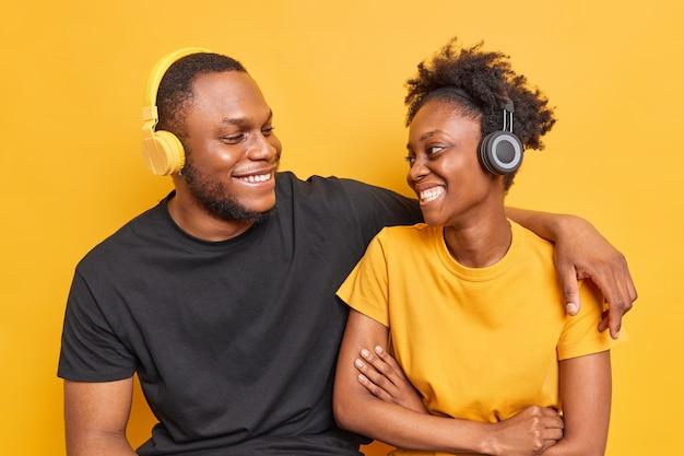 Foto de estudio de los mejores amigos con piel oscura que tienen una conversación agradable, una sonrisa, muestran felices los dientes blancos, escuchan música a través de auriculares inalámbricos