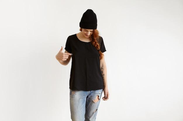 Foto de estudio de moda joven jengibre hembra caucásica con trenza vistiendo ropa elegante