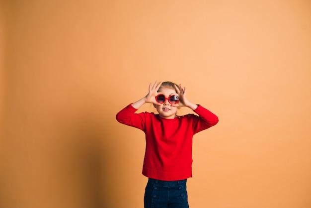 Foto de estudio de moda joven rubia de 6-7 años con gafas de sol, sobre fondo marrón claro