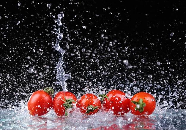 Foto de estudio con movimiento de congelación de tomates cherry en salpicaduras de agua sobre fondo negro