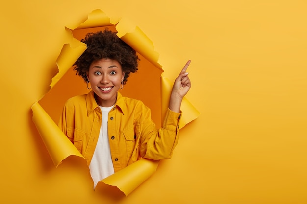 Foto de estudio de una mujer afroamericana positiva señala con el dedo para copiar el espacio de arriba, emocionado por la buena información, sonríe agradablemente, usa una chaqueta amarilla, se para en un agujero de papel rasgado.
