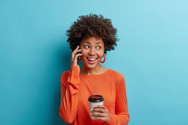 Foto de estudio de mujer afroamericana positiva toma café para llevar sonríe alegremente tiene conversación telefónica usa aretes y puente aislado sobre pared azul