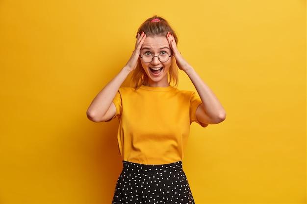 Foto de estudio de mujer alegre emocionada mantiene las manos en la cabeza y exclama con alegría por el éxito inesperado