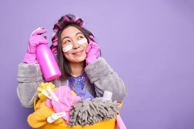 Foto de estudio de mujer asiática con expresión de ensueño aplica parches de colágeno debajo de los ojos sostiene detergente vestido con ropa doméstica posa cerca de la canasta llena de ropa aislada sobre el espacio de copia de pared púrpura